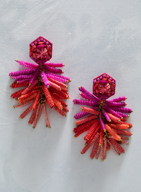 Fringed in a colorful array of glass beads, the earrings are a red-hot mix of pink and coral hues.  Clustered together with silk cording and sequins, a glass rhinestone sits atop the leather backing, with silver plated post.