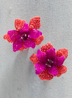 Backed in leather, intricate petals of layered sequins unfurl around a fuchsia rhinestone on the flamboyant floral earrings; sterling silver posts.