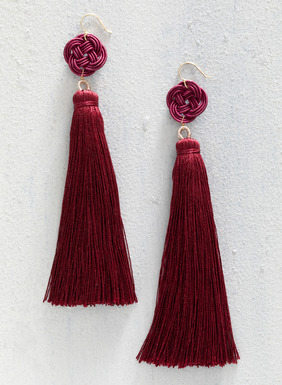 The handmade shoulder-dusting red tassel earrings are topped with Chinese knots.
