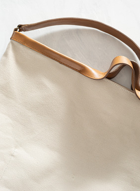 The roomy canvas tote has leather handles, a shoulder strap and inner pocket.