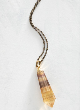This unique necklace features a yellow fluorite teardrop bottle designed to hold essential oils or perfume. The fluorite bottle is suspended on a brass chain and finished with an easy-to-use lobster claw closure.