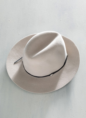 This stone-hued felt hat is thoughtfully trimmed with a thin leather black band and finished with a sleek, silver-toned bead.