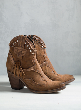 "Handcrafted in Tuscany, the cowboy booties in distressed saddle leather are detailed with scalloped eyelets, metal studs and fringe. Stacked wood 3"" heel; side zip."