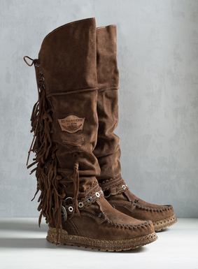 "The knee-high moccasin boots are artisan-crafted in Tuscany of slouchy caramel suede. Detailed with 2½"" hidden wedge heels, back lacing, fringe, scalloped eyelet trim and buckling straps."