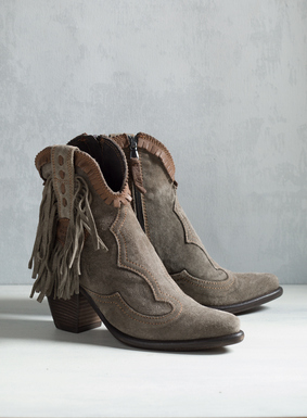 "Handcrafted in the foothills of Tuscany, the stylish cowboy booties in soft truffle suede are detailed with brown leather trim and dramatic fringe. Stacked wood 3"" heel; side zip."