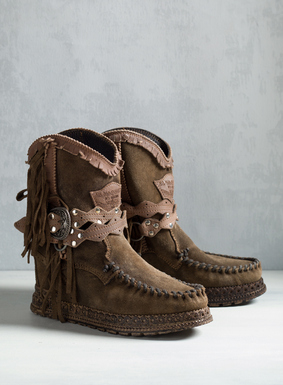 "Our Tobacco suede moccasin booties are handcrafted in Italy, with buckling leather straps, fringed trim and a comfy, hidden 2½"" wedge heel. <a href=""/category/seasonal+trends/el+vaquero.do"">Read more about El Vaquero footwear and why their craftsmanship is unmatched.</a>"