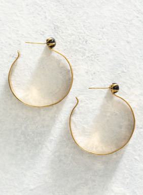 Hoop earrings in hammered brass, set with a deep blue goldstone.